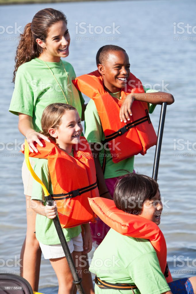 Summer camp counselor with children and kayak stock photo