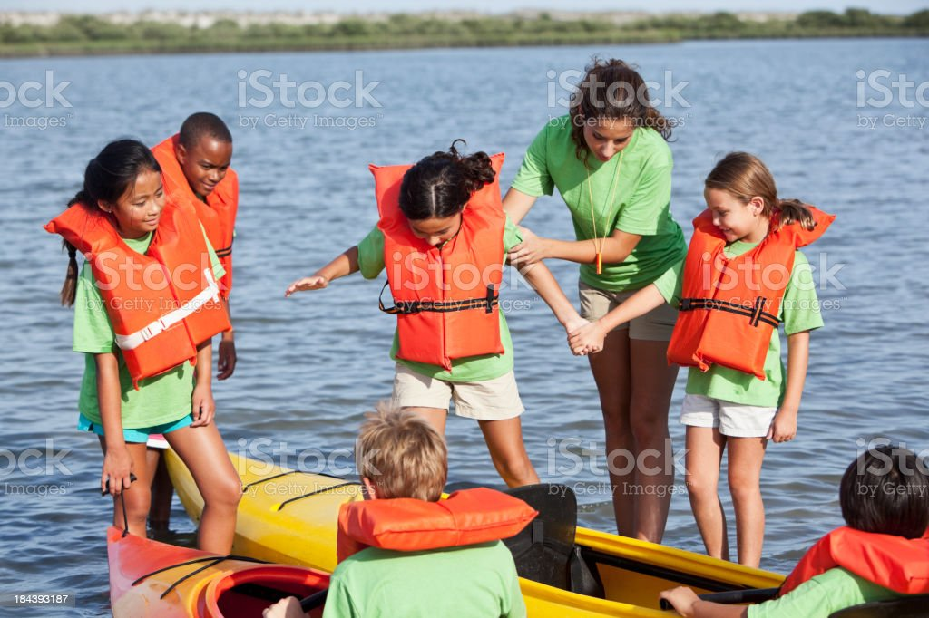 Summer camp counselor with children and kayaks stock photo