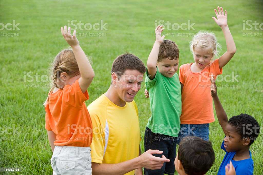 Summer camp counselor with diverse goup of children stock photo