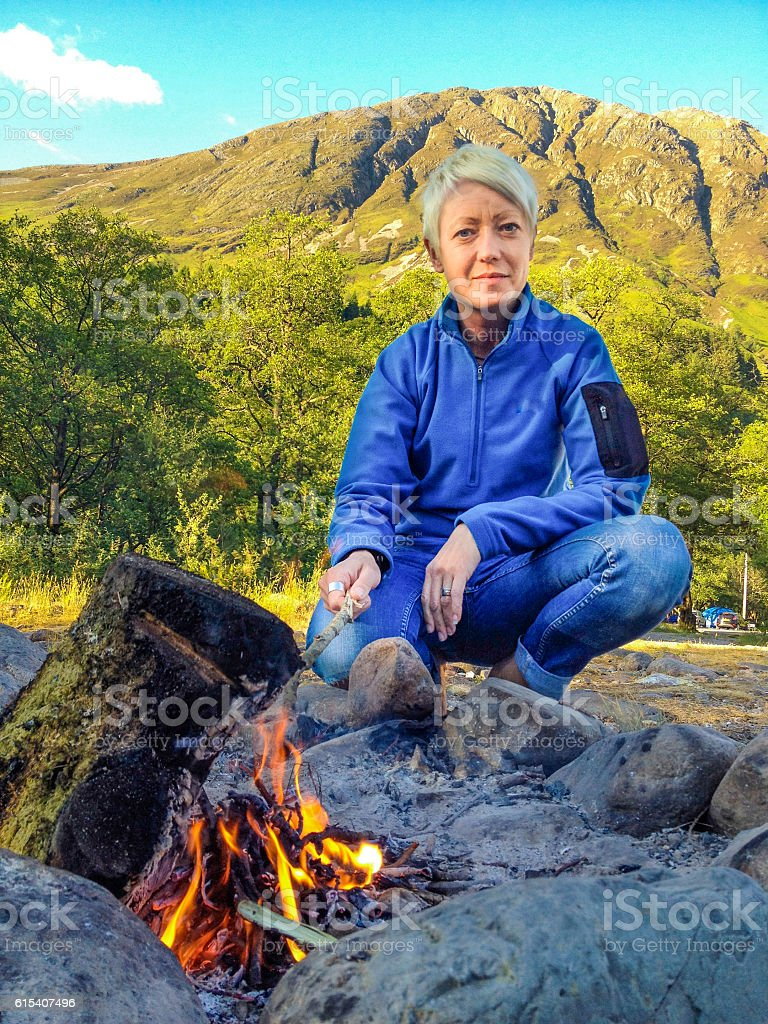 Summer Camp Fire Heating Pretty Woman Camping Glencoe Scotland stock photo
