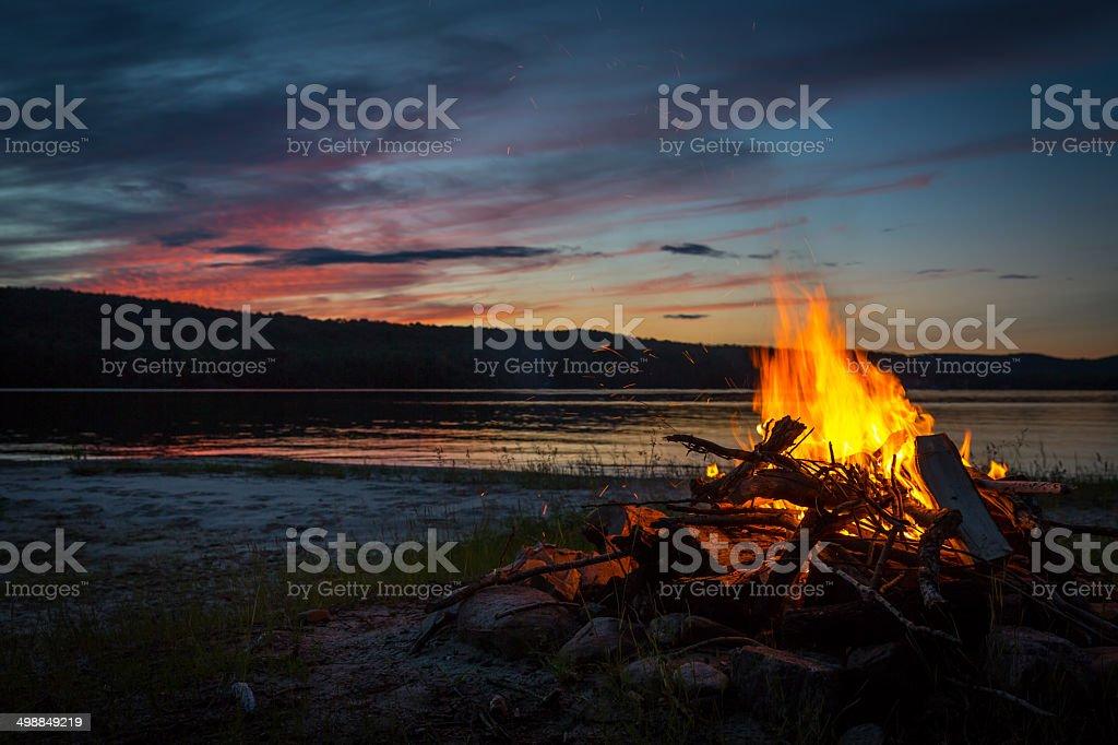 Summer Campfire and Lake at sunset stock photo
