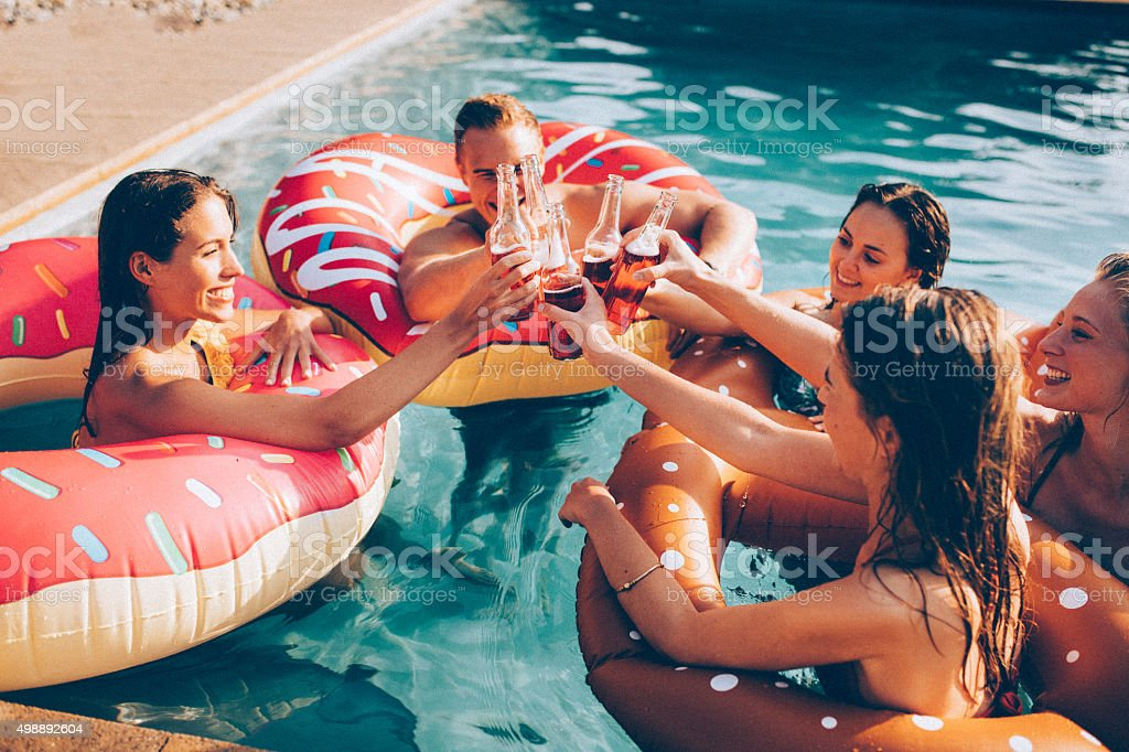 Summer celebration with some friends and colourful drinks in pool stock photo