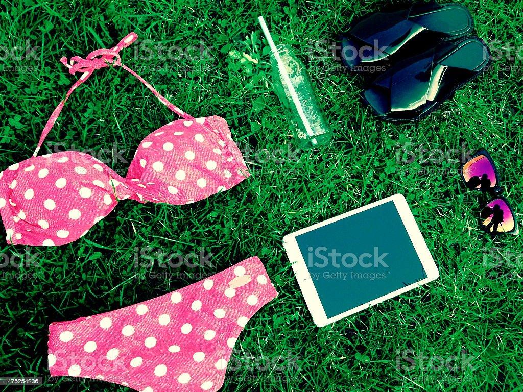 summer clothes swimsuit, tablet, sunglasses, flip flops, glass bottle stock photo