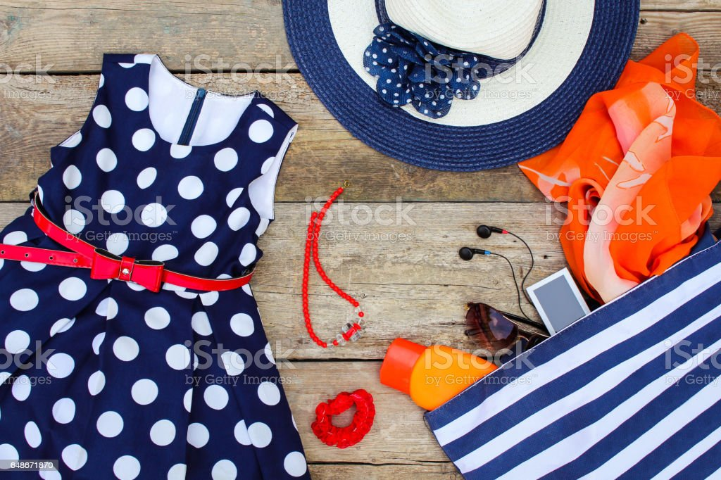 Summer clothing and accessories: dress, handbag, headphones, perfume, sunglasses, sunscreen, bonnet and beads. stock photo