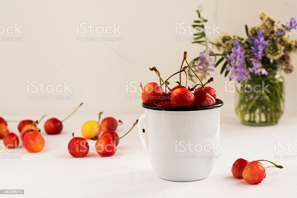 Summer composition with fresh sweet cherries and wild flowers stock photo
