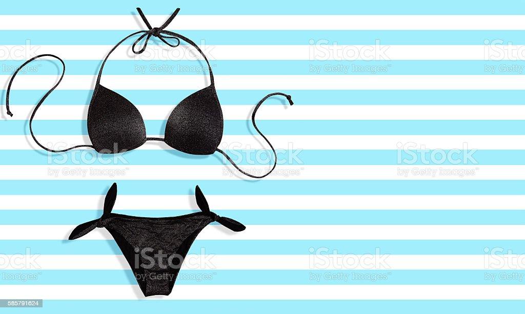 Summer fashion.Black bikini swimwear on blue stripe background. stock photo