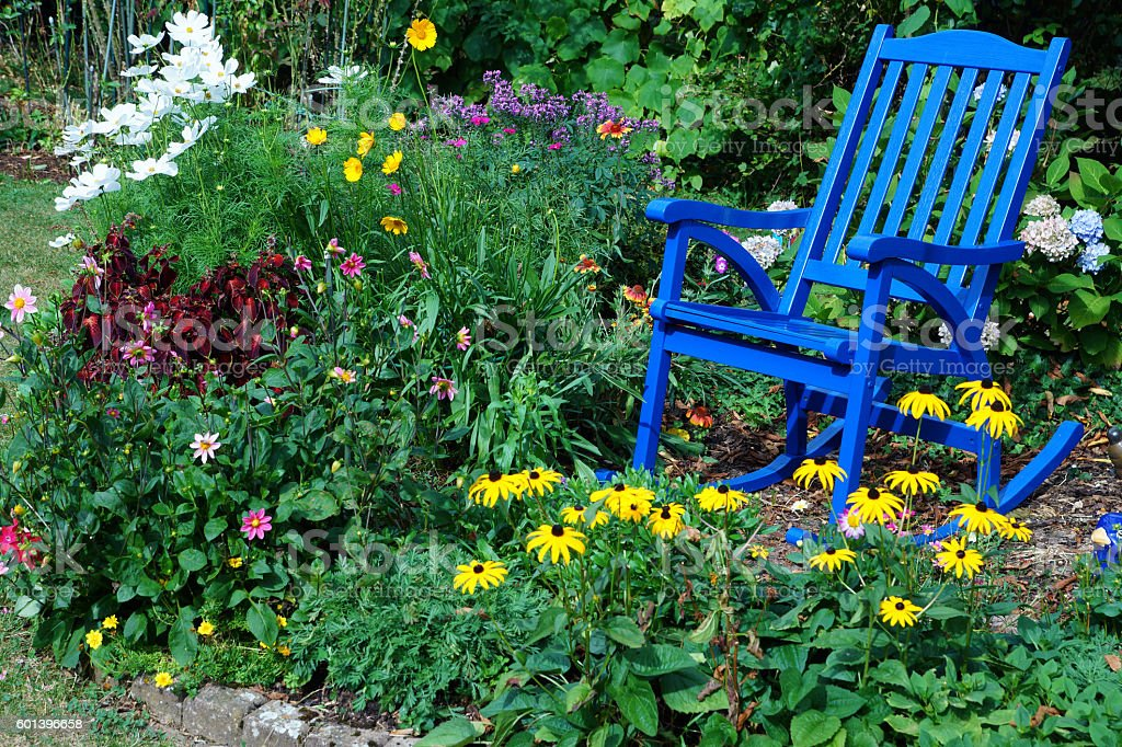 Summer flowers and a blue rocking chair stock photo