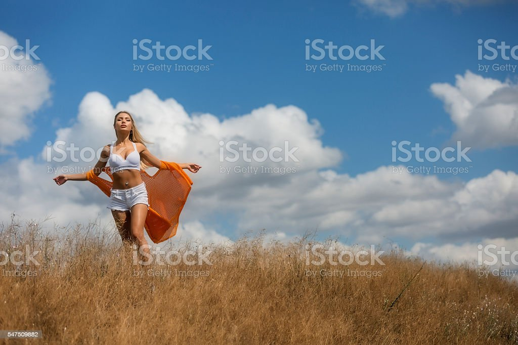 Summer freedom. Young woman sunbathing at dry meadow stock photo
