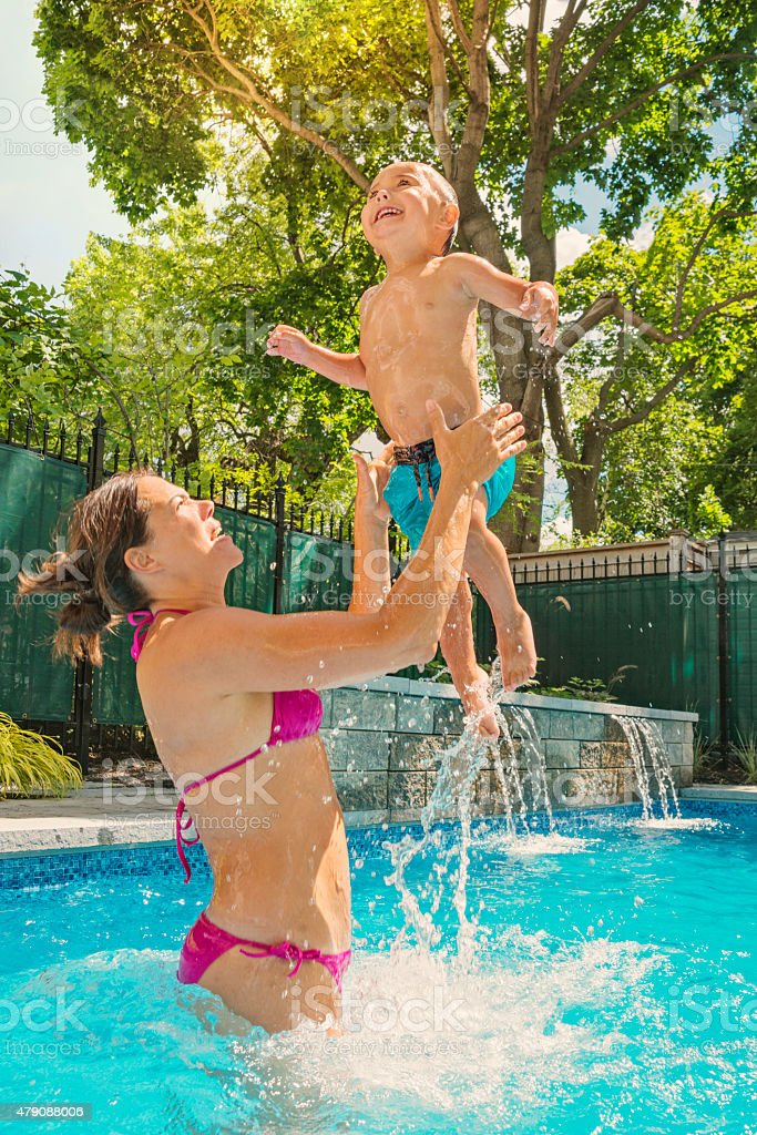 Summer fun for mother and son in the backyard pool. Mom is throwing...