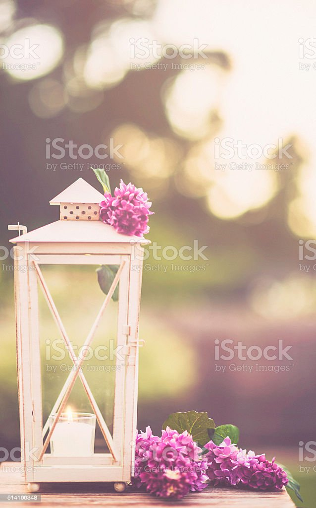 Summer garden lantern illuminated by late afternoon sun stock photo