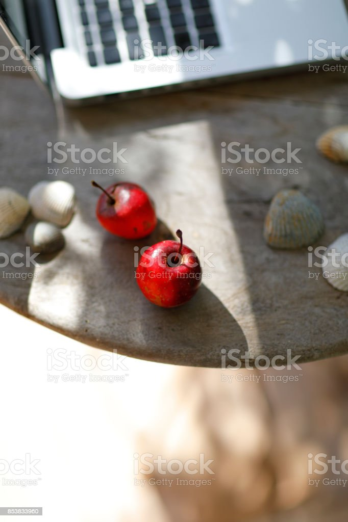 Two small red apples from an uncultivated tree on a wooden garden...