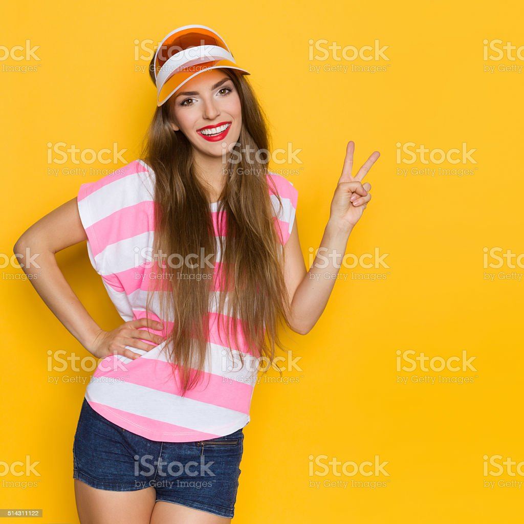 Summer Girl In Sun Visor Showing Peace Sign stock photo