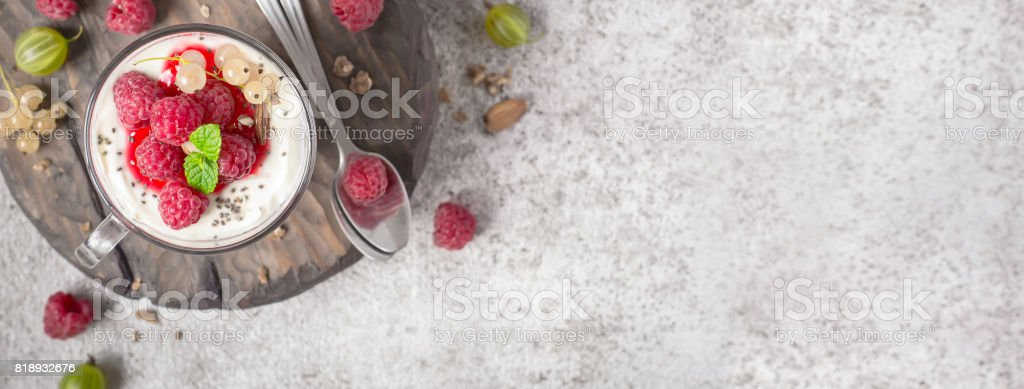 Summer healthy dessert with raspberries and yogurt on the cutting board. Banner format stock photo