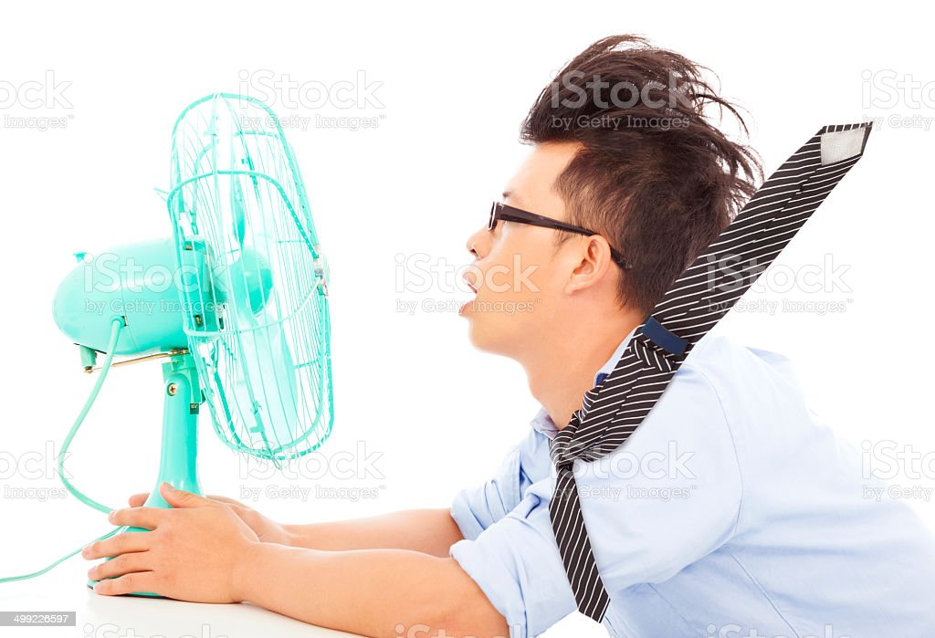 Summer heat, business man use fans to cool down stock photo