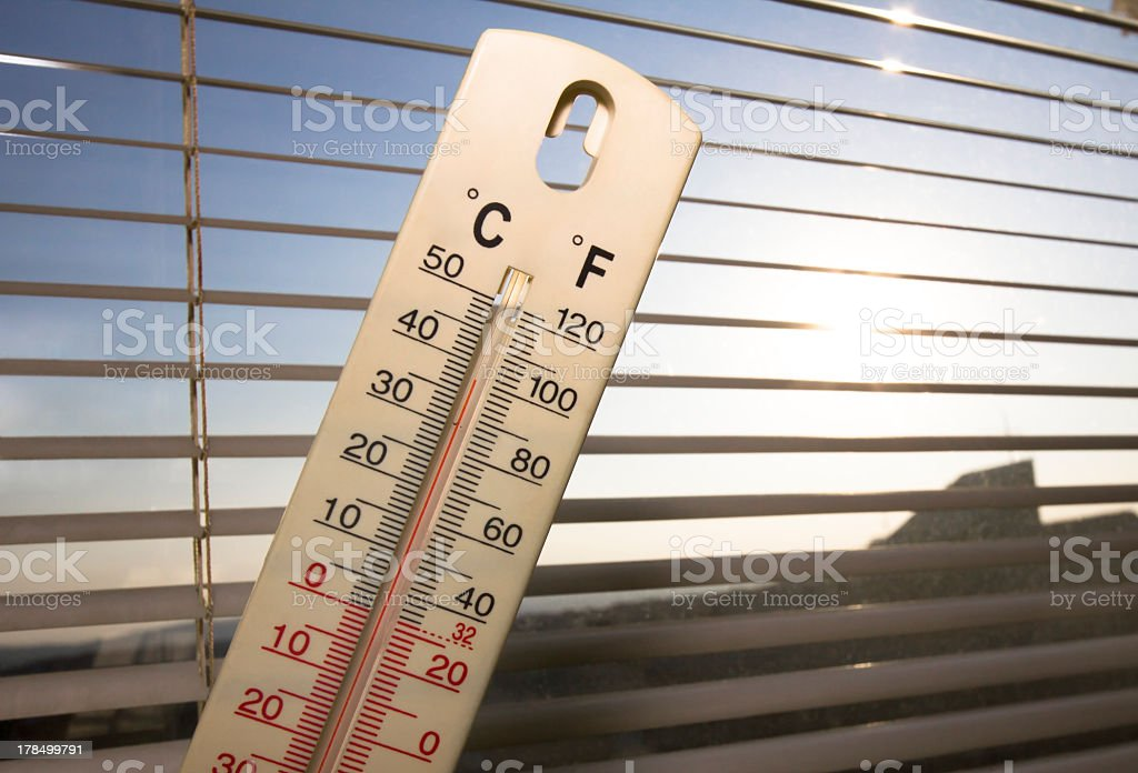 summer heat in the city, shown on mercury thermometer stock photo