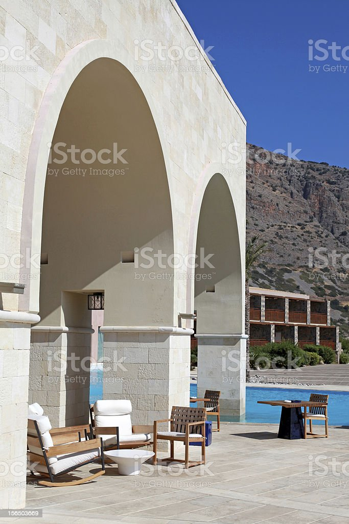 Summer hotel terrace with pool, outdoor wood chairs and table in a...