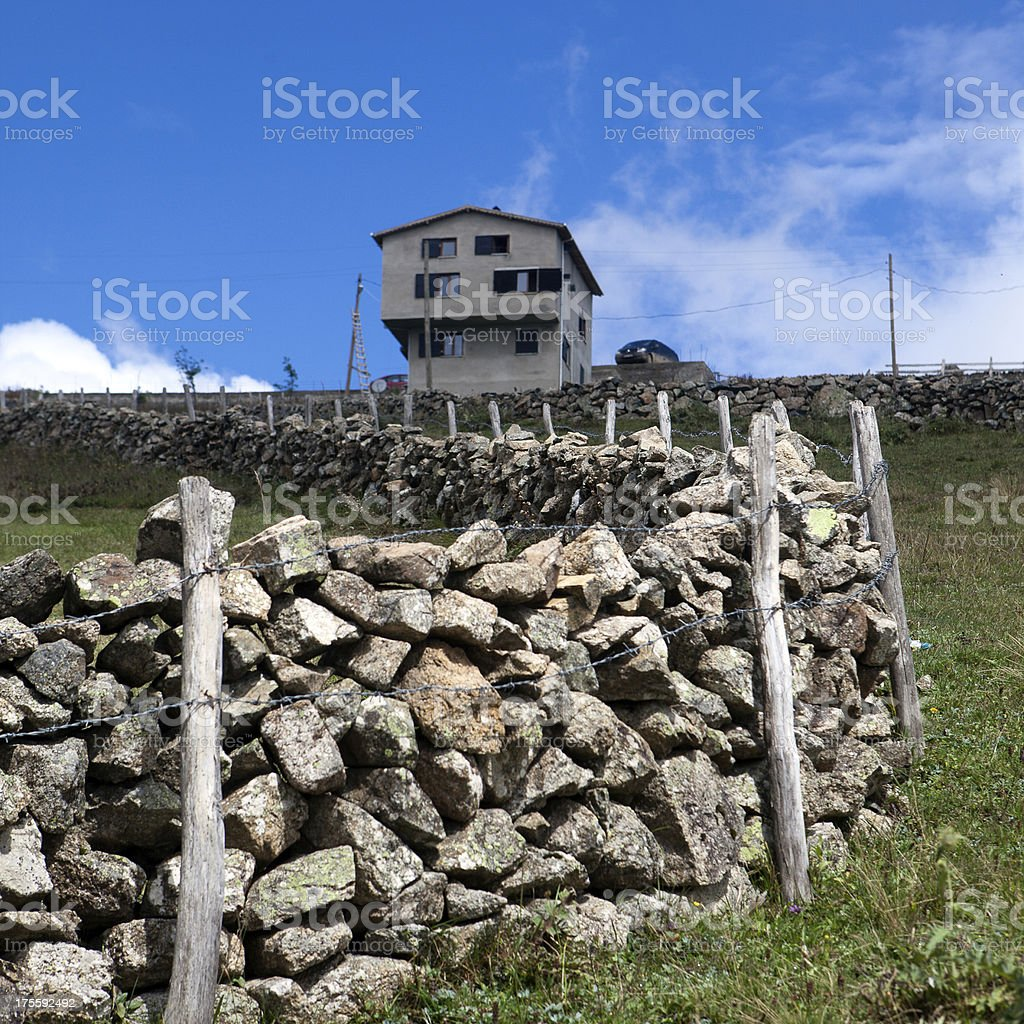Summer house and stone fence royalty-free stock photo