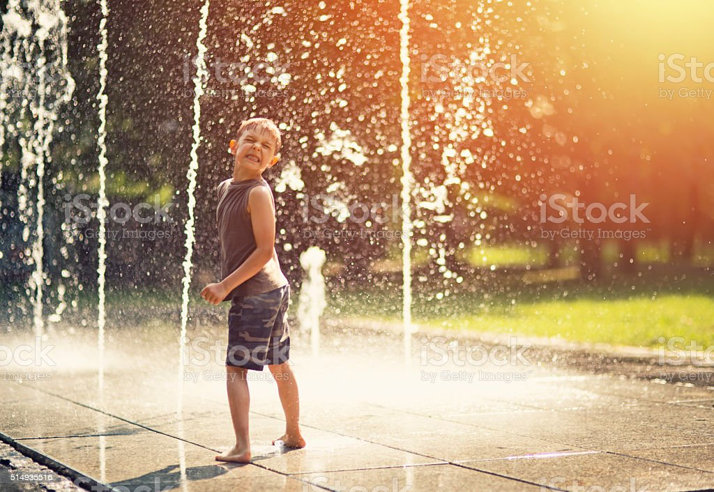 Summer in the city - little boy playing with fountain stock photo