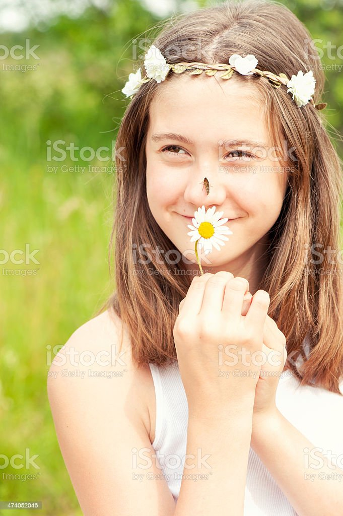 Summer is coming. Girl with butterfly on nose smelling camomile . stock photo