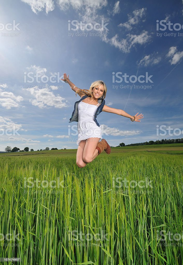 Summer Joy - Girl jumping out in the field royalty-free stock photo