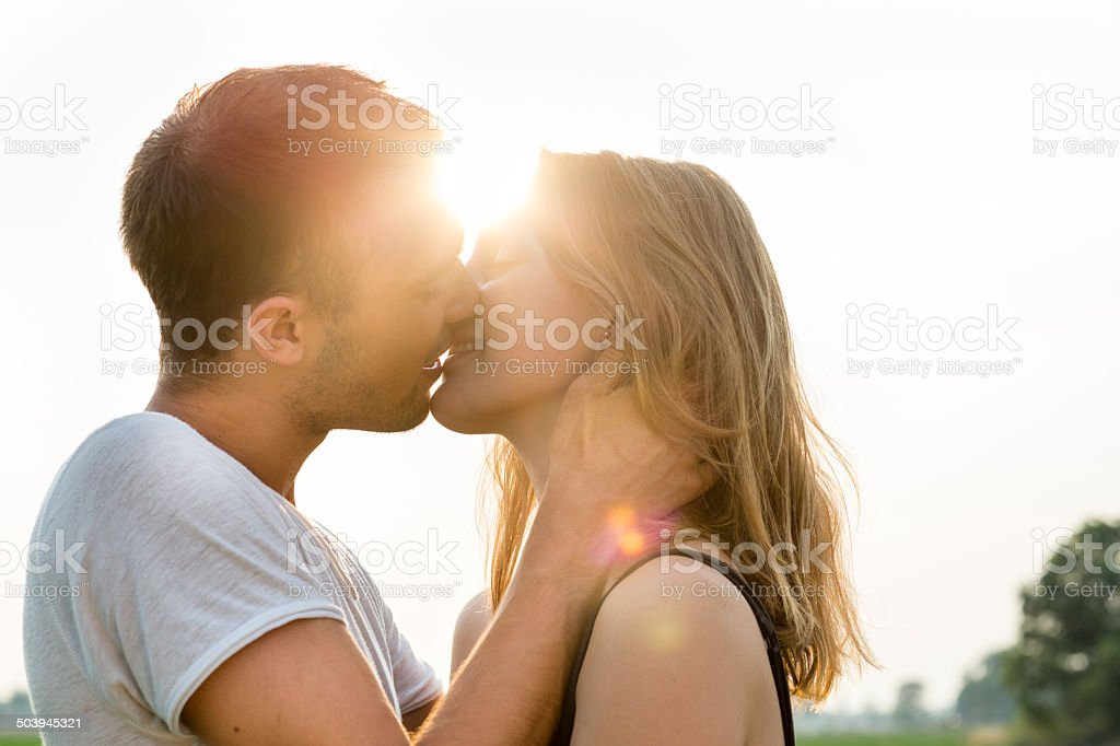 summer portrait of a kissing young adult couple, back lit stock photo