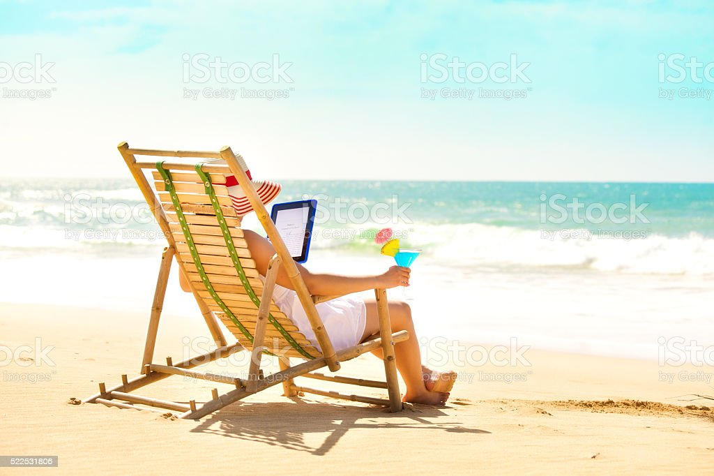Summer Reading with Digital Tablet E-Reader on Summer Beach stock photo