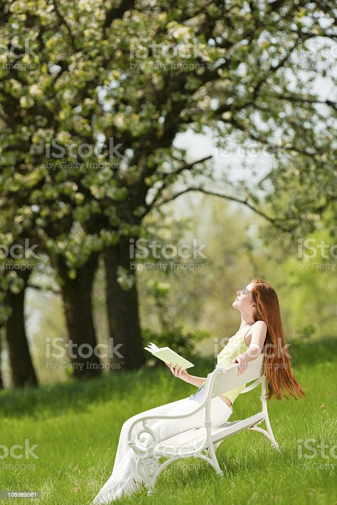 Red hair woman relax on white bench in spring orchard royalty-free stock photo