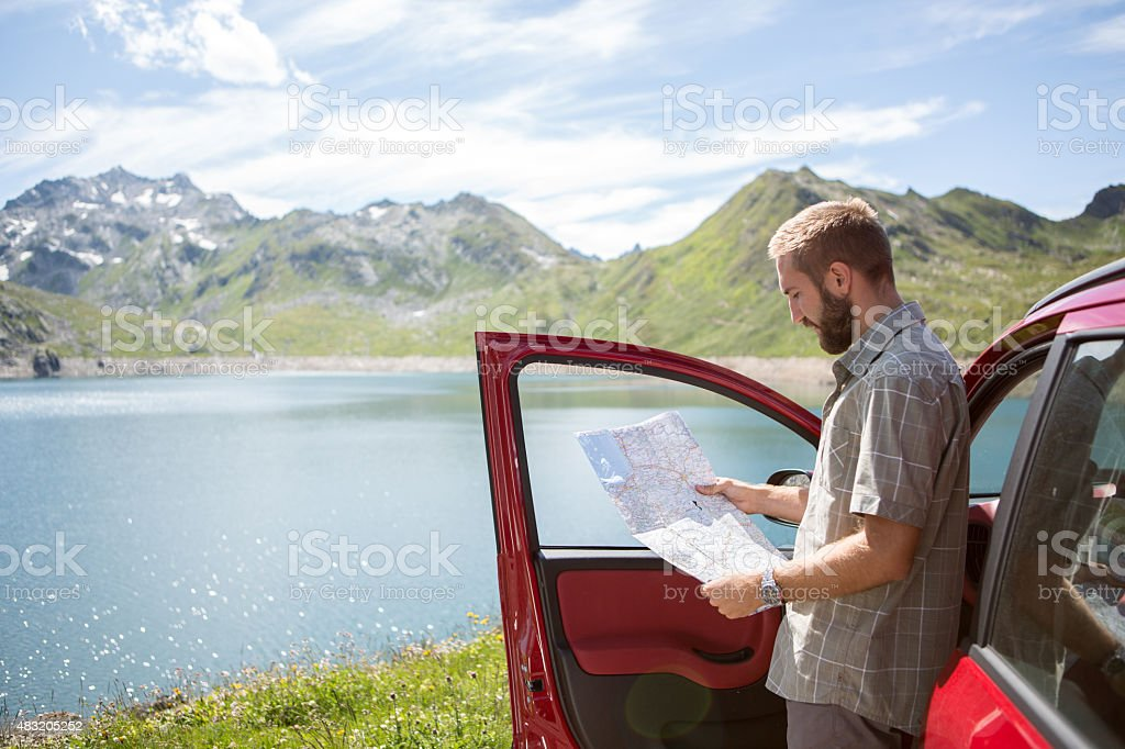Young man on a road trip in Switzerland reading a map for directions....