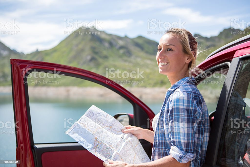 Young woman on a road trip in Switzerland reading a map for...