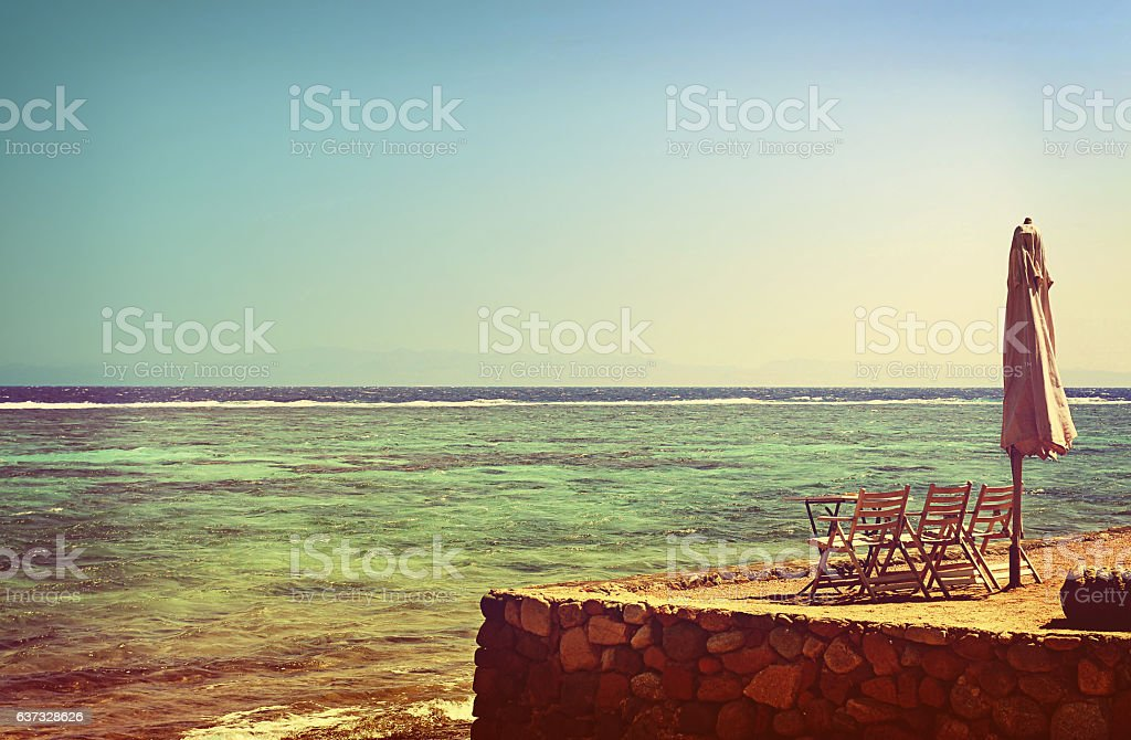 Summer seascape. Sunshade, table and chairs on bank of sea stock photo