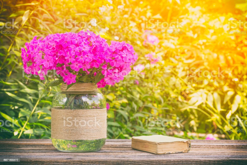 summer still life of bouquet of flowers Phlox and little old books on wooden table on natural Sunny background, tinted photo stock photo