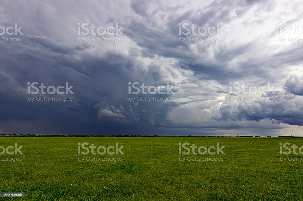 Summer Storm clouds above meadow with green grass stock photo