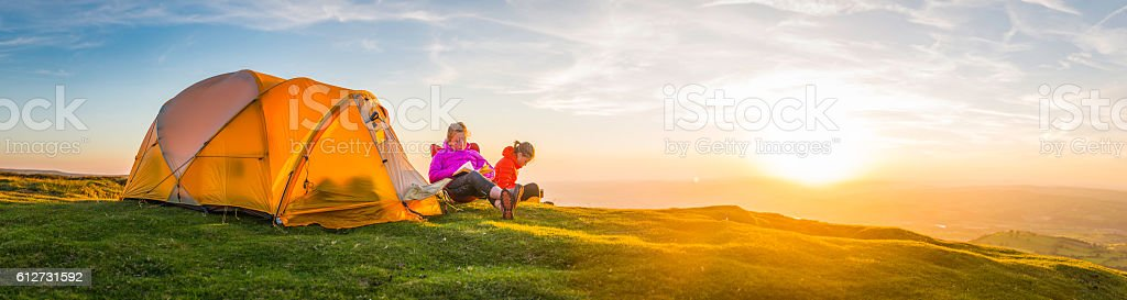 Summer sunset camping young hikers beside mountain top tent panorama stock photo