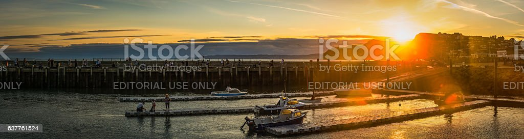 Summer sunset families fishermen boats harbour panorama West Bay Dorset stock photo