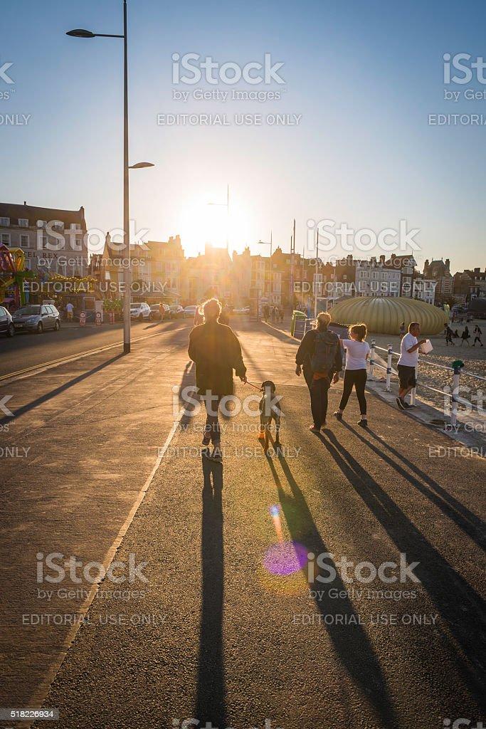Summer sunset holidays seaside tourists walking along promenade Weymouth Dorset stock photo