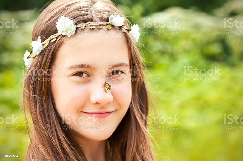 Summer surprise. Girl with floral headband on head and butterfly stock photo