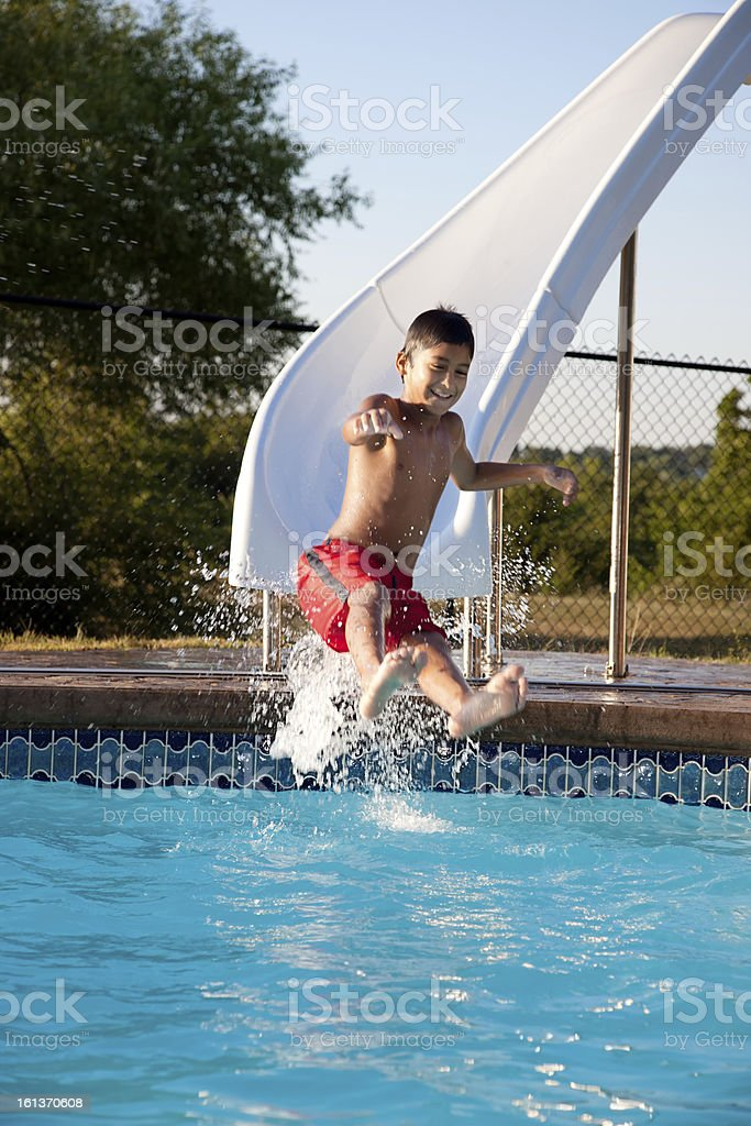 Summer Swimming: Hispanic Little Boy Playing Water Slide  Outdoors stock photo