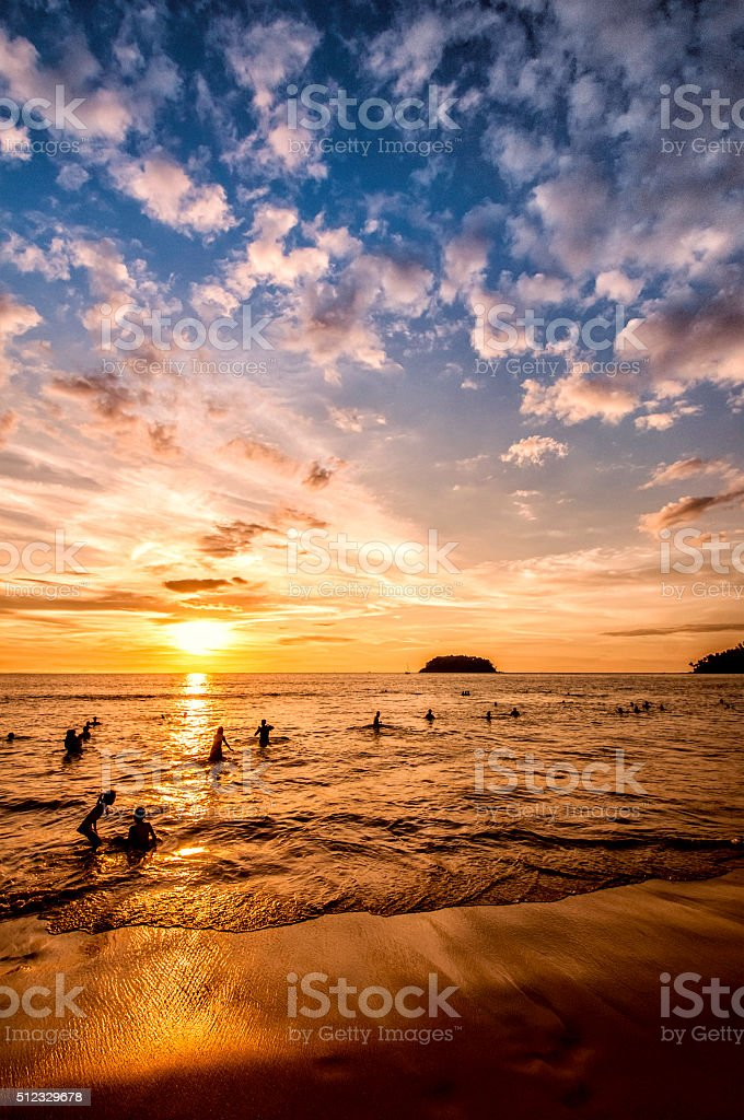 Summer Swimming on Tropical Beach at Dramatic Sunset stock photo