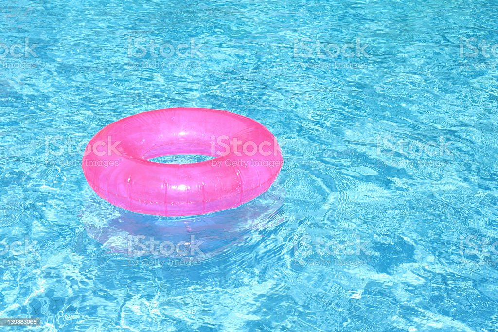 Summer swimming pool with bright pink floating ring stock photo