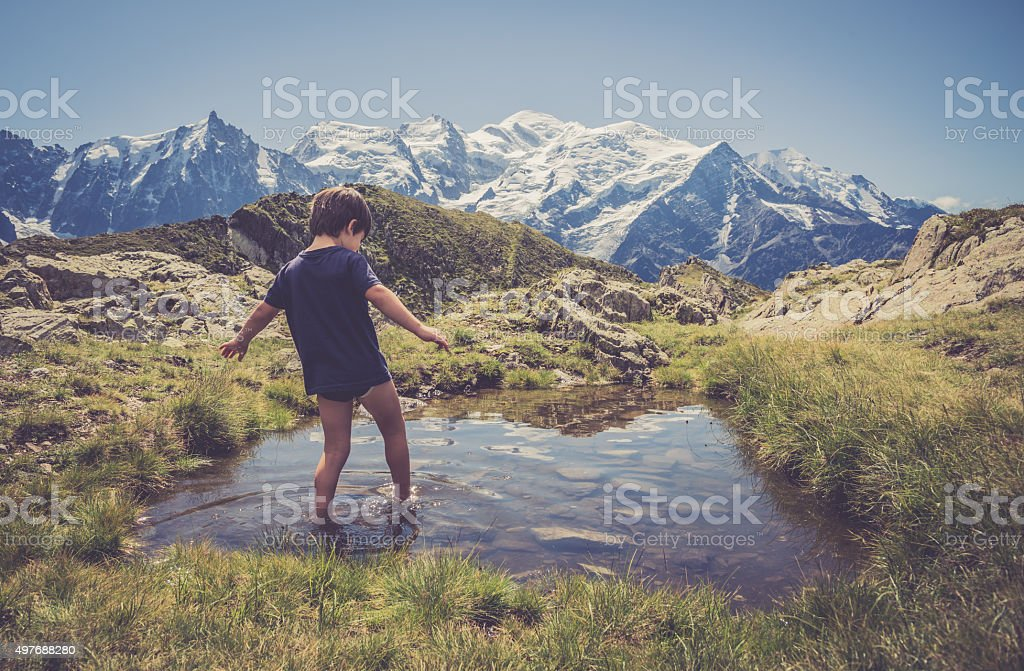Summer time. Walking in water with background Mont Blanc. stock photo
