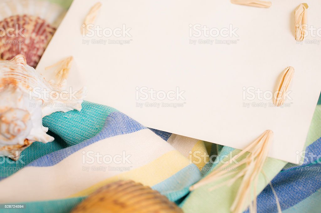 Summer vacation.  Blank, white notecard with seashells, beach blanket. stock photo