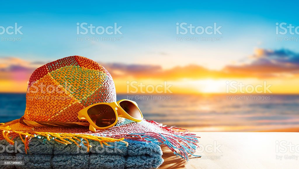 Summer vacation image with copyspace. Hat, yellow sunglasses on beach. stock photo