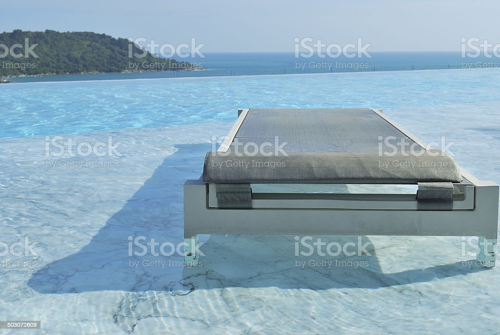 Summer vacation pool chairs on swimming pool seaview stock photo