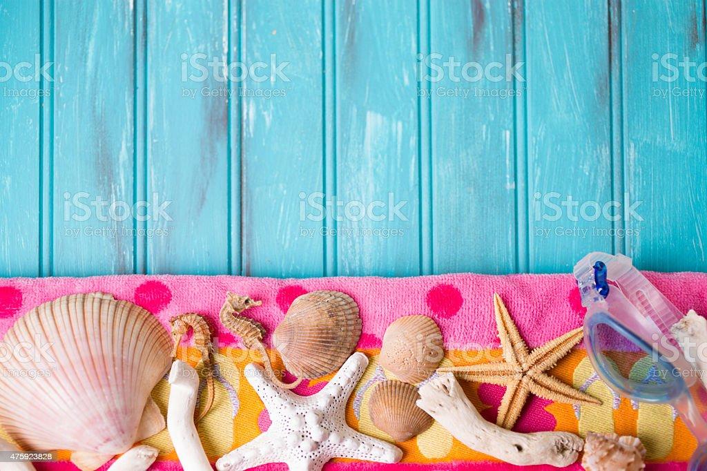 Summer vacation scene. Seashells on beach towel. Blue background. stock photo