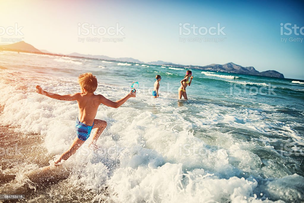Summer vacations - kids playing at sea stock photo