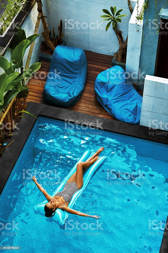 Summer Vacations. Woman Sunbathing, Floating In Swimming Pool Water stock photo