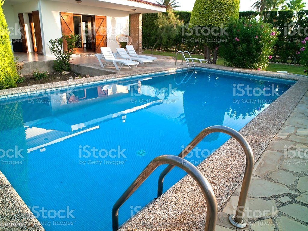 Summer villa with in-ground pool and landscaped deck stock photo