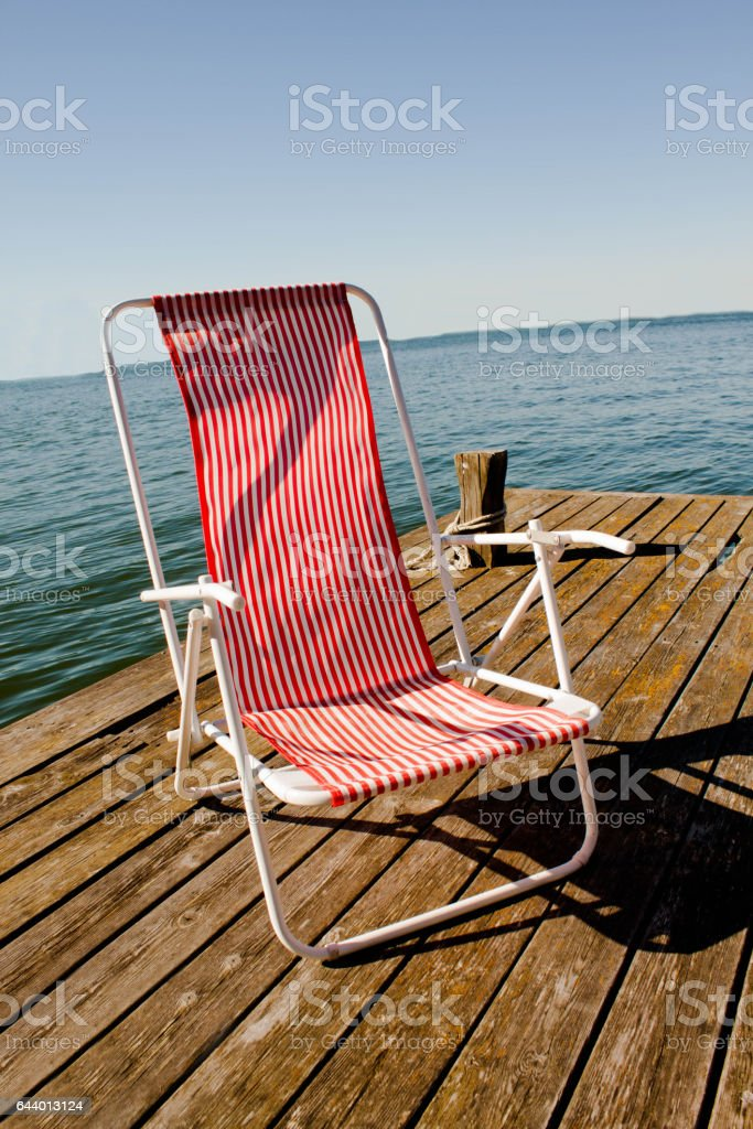 summer vintage chair in the pier at the lake stock photo
