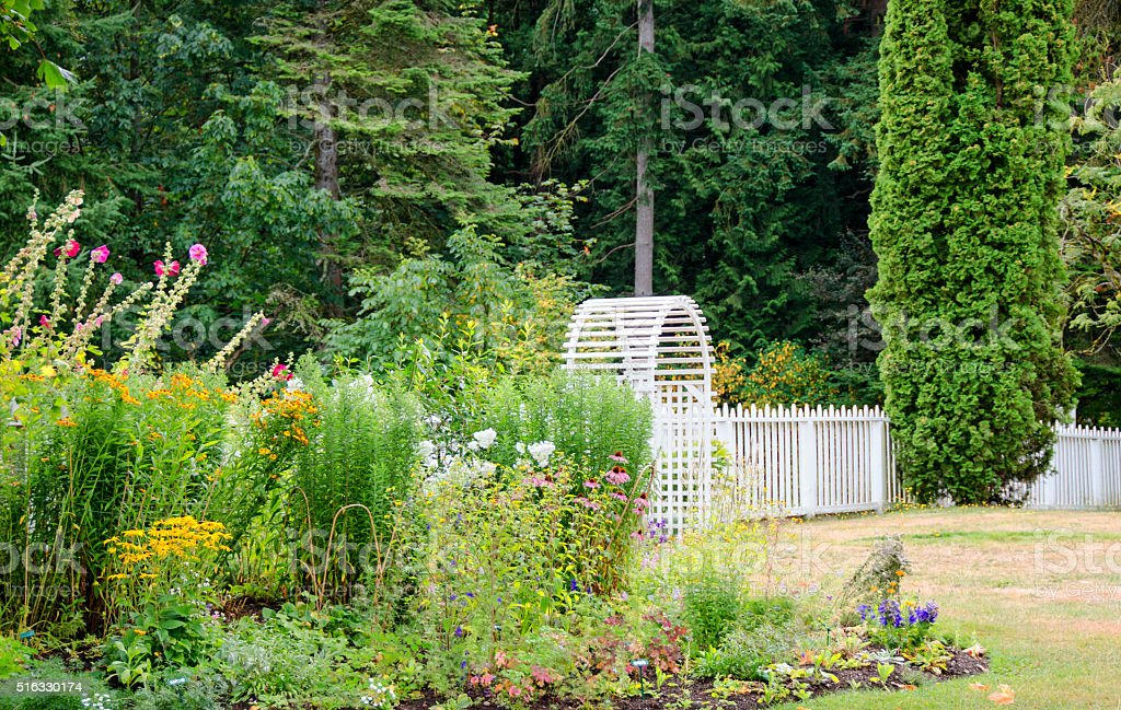 Summer white garden gate and arched entry- flowers stock photo
