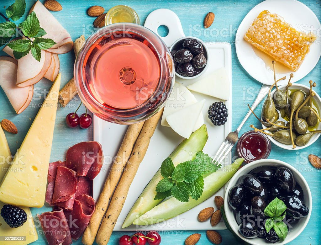 Summer wine snack set. Glass of rose, meat, cheese, olives stock photo